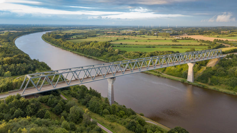A bridge crossing the Kiel Canal (German: Nord-Ostsee-Kanal) in Schleswig Holstein in Germany with lush green fields and wind farms in the background is captured aerial from a drone at sunset.