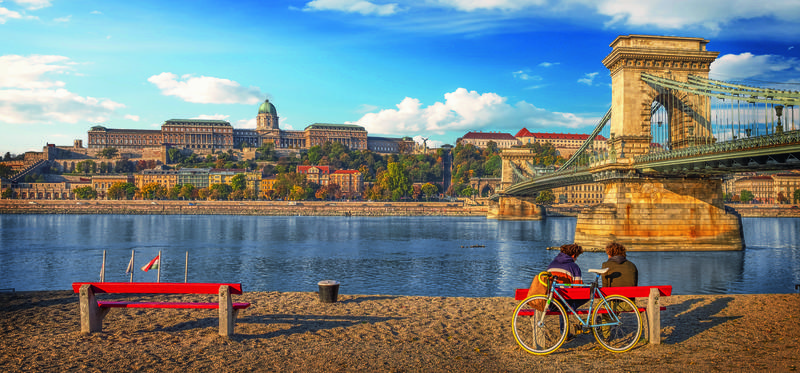A couple enjoying the view while sitting on a bench near the Danube river embankment in Budapest, Hungary