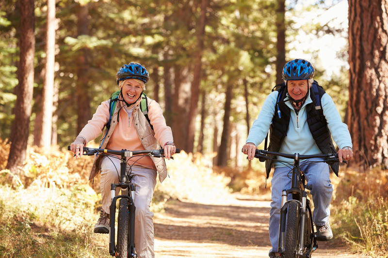 Senior couple cycling on forest trail, California